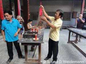 Herr Tu zündet eine Räucherspirale für Seite Touristengruppe an